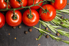Branch of cherry ripe tomatoes, fresh rosemary, allspice, food photography stock photos