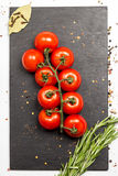 Branch of cherry ripe tomatoes, rosemary, allspice, anise, food photography Royalty Free Stock Photos