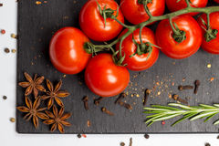 Branch of cherry ripe tomatoes, rosemary, allspice, anise, food photography Stock Image