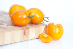 The branch of cherry tomatoes. On white Stock Photography