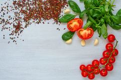 Branch of cherry tomatoes, basil, garlic and various pepper on the gray background. Top view with copy space. For text royalty free stock photo