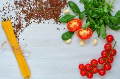Branch of cherry tomatoes, basil, garlic, various pepper and uncooked pasta on the gray background. Top view with copy space. For text stock photos