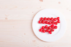 Branch of cherry tomatoes in a white plate on a light wooden tab Royalty Free Stock Photo