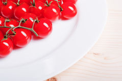 Branch of cherry tomatoes in a white plate on a light wooden tab Royalty Free Stock Photography