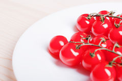 Branch of cherry tomatoes in a white plate on a light wooden tab Stock Image