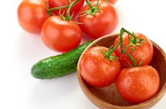 The branch of cherry tomatoes in a wooden bowl Stock Images