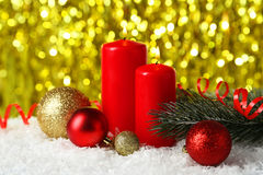 Branch of Christmas tree with balls and candles on snow Royalty Free Stock Image