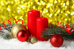 Branch of Christmas tree with balls and candles on snow, close up Stock Images