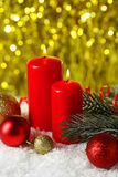Branch of Christmas tree with balls and candles on snow, close up Royalty Free Stock Images