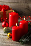 Branch of Christmas tree with balls and candles on wooden background Stock Image