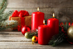 Branch of Christmas tree with balls and candles on wooden background Stock Images
