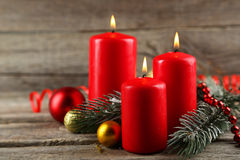 Branch of Christmas tree with balls and candles on wooden background Royalty Free Stock Photos