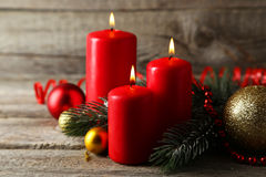 Branch of Christmas tree with balls and candles on wooden background Stock Photos