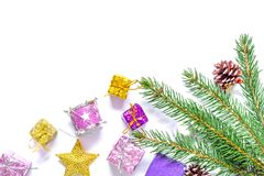 Branch of a Christmas tree with balls, fir cones, traditional candies and boxes with gifts isolated on white background. Christmas and New Year background Royalty Free Stock Photo