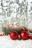 Branch of Christmas tree with balls on snow, close up Royalty Free Stock Photos