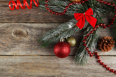 Branch of Christmas tree with balls on wooden background Stock Images