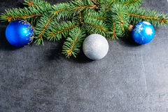 Branch of a Christmas tree and blue ball. On dark stone background Stock Images