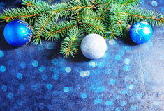Branch of a Christmas tree and blue ball. On dark stone background with blue bokeh Royalty Free Stock Image