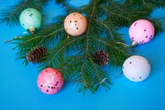 A branch of a Christmas tree, cones and colorful balls on a blue background. Close-up. Merry Christmas and Happy New Year. 2019 royalty free stock photo