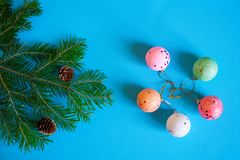 Branch of a Christmas tree, cones and colorful balls on a blue background. Merry Christmas and Happy New Year. 2019 stock photography