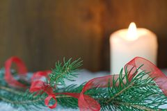 Branch of Christmas tree with red ribbon. And a burning candle in snow Stock Photos