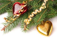 Branch of Christmas tree with short needles decorated  toys in the form  heart isolated on white background Stock Images