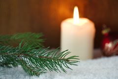 Branch of Christmas tree in snow. Branch of Christmas tree with a burning candle and Christmas ball in snow Stock Photos