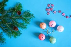 A branch of a Christmas tree, snowflakes, cones and colorful balls on a blue background. Waiting for the holiday. Merry Christmas and Happy New Year - 2019 stock image