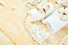 Branch of cotton plant, eared sticks, cotton pads. Towel, cosmetic makeup removers tampons, hygienic sanitary swabs on wooden background Top view. Spa concept royalty free stock images