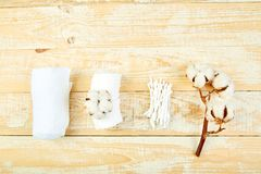 Branch of cotton plant, eared sticks, cotton pads. Towel, cosmetic makeup removers tampons, hygienic sanitary swabs on wooden background Top view. Spa concept royalty free stock photo