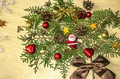 Branch of cypress with a toy plush Santa Claus frost,chocolate balls and hearts. Cones and satin bows on a wooden plywood Royalty Free Stock Images