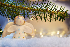 Branch, felt angel on snow and bokeh lights Royalty Free Stock Images