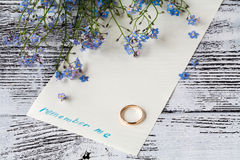 Branch of forget-me-nots on paper with phrase remember me stock image