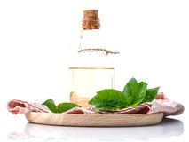 Branch of fresh  basil in wooden plate with olive oil . Stock Photos