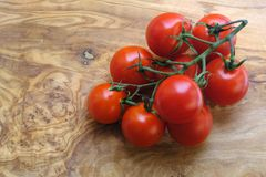 Branch of fresh cherry tomatoes on wood. Good quality close up photo of fresh ripe cherry tomatoes on green branch served on some wooden surface. Tomatoes are Stock Image