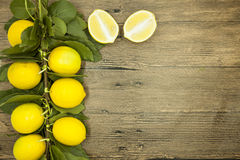 Branch of fresh juicy Sicilian lemons on a wooden background Royalty Free Stock Image