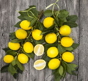 Branch of fresh juicy Sicilian lemons on a wooden background Stock Photos