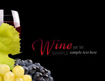Branch of grapes and glass of wine. Isolated on black background Royalty Free Stock Photos