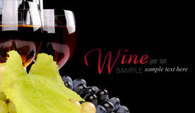 Branch of grapes and glass of wine. Isolated on black background Stock Photography