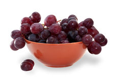 Branch of grapes in orange bowl isolated Royalty Free Stock Image