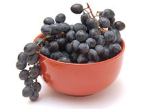 Branch of grapes in the red bowl Stock Photo