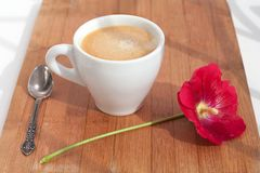Branch of mallow red flower and white cup of hot coffee with foam with silver spoon on table on wood background closeup royalty free stock images