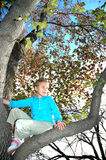Branch Out. An eight year old girl climbs up in a tree. A girl exploring and having fun outside in nature. Happy child in a tree Royalty Free Stock Photography