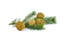 Branch of a pine with Christmas tree decorations. Green pine branch decorated with four balls of Christmas tree decorations. Three balls made of straw and a one Stock Photos