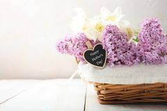 Branch of purple lilac and white anemone flower in basket. On wooden table on neutral background. Concept mother`s day.  Copy space stock photo