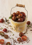 Branch of red ripe cherry tomatoes in a yellow,  ceramic. Branch of red ripe cherry tomatoes in a yellow, little, ceramic bucket Stock Photo
