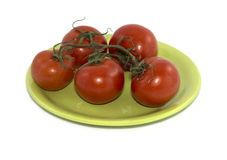 Branch of red tomatoes on a lime plate Stock Photo