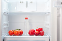 Branch of red tomatoes, two red peppers, two two-colored orange and red peaches and a bottle of water on shelf of open empty refri Stock Image