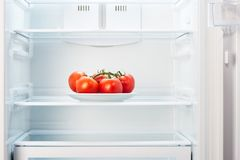 Branch of red tomatoes on white plate in open empty refrigerator stock photography