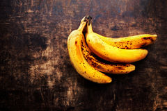 A branch of rotten ripe bananas on vintage wooden background. Ov Royalty Free Stock Photos